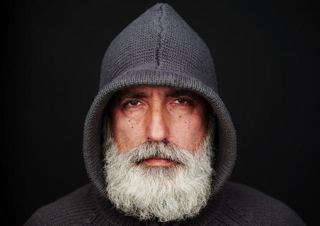 portrét: Portrét starší muž v pletené bundě na černém pozadí. orientace na šířku