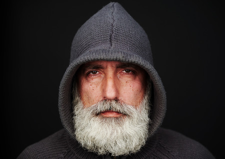 close portrait: portrait of senior man in knitted jacket over black background. landscape orientation Stock Photo