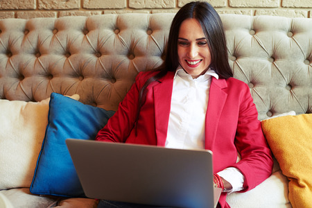 relaxing at home: smiley businesswoman resting with laptop on sofa