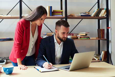 concentrated man and woman looking at laptop in office