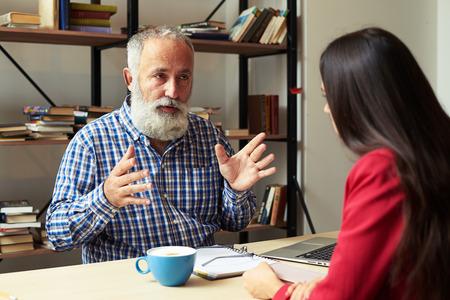 patron: jefe explicando algo a trabajador joven en su oficina Foto de archivo