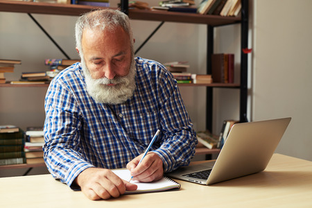 bearded senior man writing in notepad at his working place