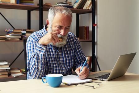 senior writer eating cookies and working in his room Foto de archivo