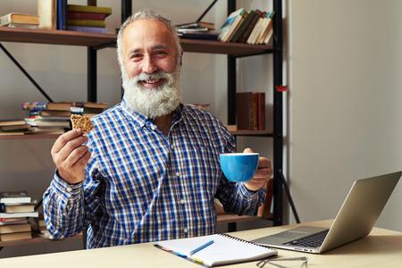 hombre comiendo: alegre hombre de negocios que tiene descanso para tomar café en su lugar de trabajo