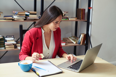 young woman working with laptop and eating cookies in office