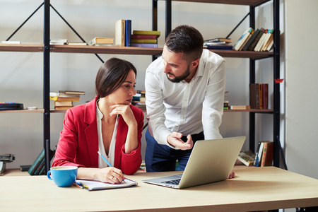project manager: businessman explaining something to woman and looking at her, woman listening and looking at laptop in office Stock Photo