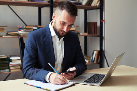 man at work: young businessman holding his smartphone and writing on notepad in office Stock Photo