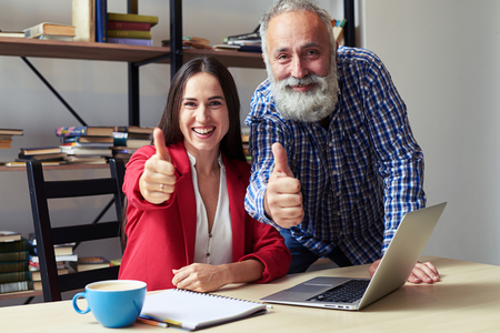 work  office: smiley businesswoman and senior businessman showing thumbs up and looking at camera in office