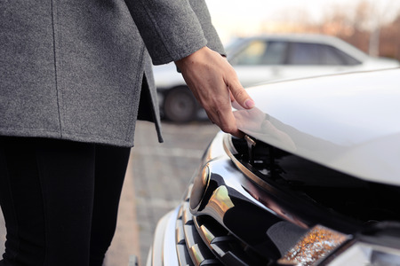 bonnet up: closeup photo of womans hands open the bonnet at outdoor Stock Photo