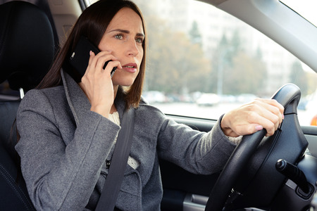 phone conversation: serious young woman driving his car and talking on the phone Stock Photo