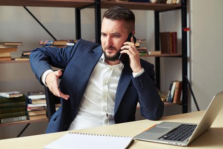 displeased: displeased businessman talking on the phone in office