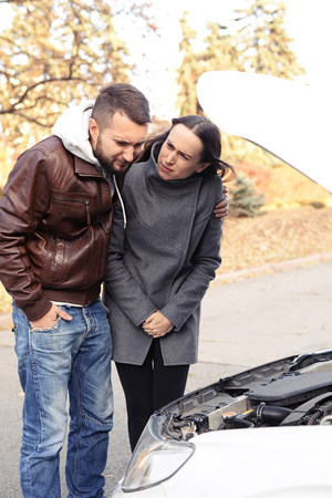 discontented: worried man looking under the hood of breakdown car, woman looking at him at outdoor