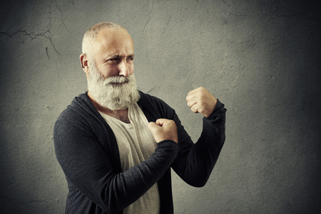 suspiciously: funny bearded man standing in boxing pose over grey wall Stock Photo