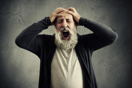 hombres maduros: gritando hombre mayor con los ojos cerrados, sosteniendo la cabeza con las manos sobre fondo gris