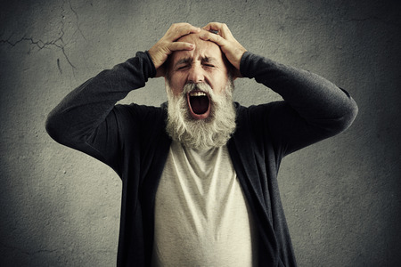 elderly people: screaming senior man with closed eyes holding his head by hands over grey background Stock Photo