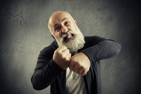 screaming: angry screaming senior man with beard over dark wall