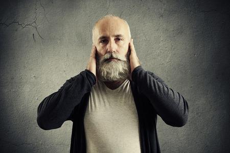 old man beard: bearded senior man covering his ears and looking at camera over dark wall Stock Photo