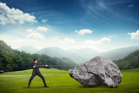 pulling beautiful: businessman in formal wear pulling the big stone at outdoor over beautiful landscape Stock Photo