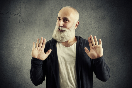 restrictions: senior bearded man showing refusal sign and looking at camera over dark background