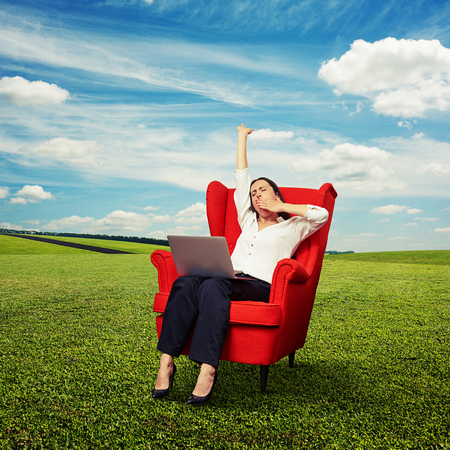 tiresome: tired businesswoman sitting in red chair with laptop and yawning at outdoor Stock Photo