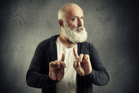 interdict: senior bearded man showing refusal sign and looking at camera over dark wall