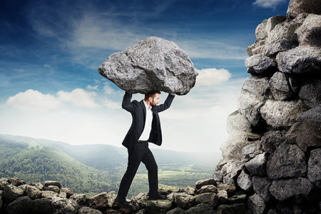 businessman in formal wear holding big stone and walking on the mountains Standard-Bild