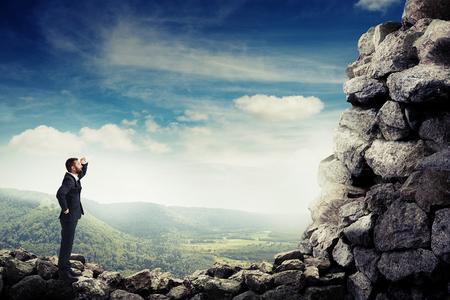 personas mirando: hombre de negocios sonriente sosteniendo su mano cerca de la frente y mirando a la montaña de piedra