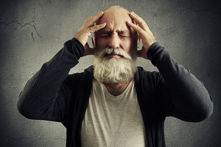 emotional bearded man holding his head and wincing in pain over grey background Stock Photo