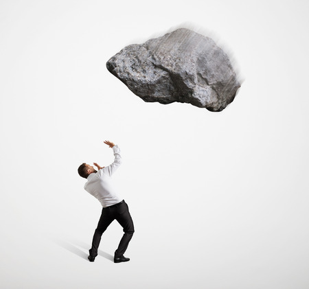 one man: scared businessman under big flying stone over light grey background Stock Photo