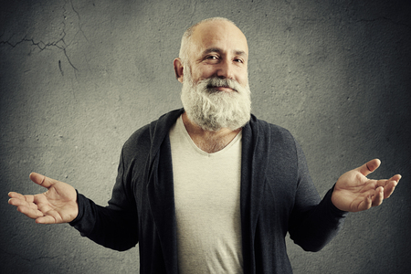 white beard: smiling good-natured man looking into the camera and waved his hands over grey wall