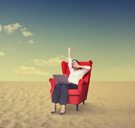 tiresome: yawning businesswoman with laptop on chair working in desert