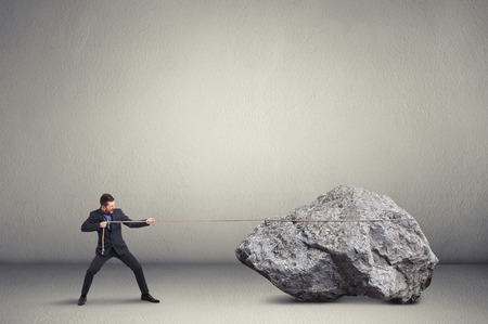 business rival: businessman in formal wear pulling the big stone over light grey background Stock Photo