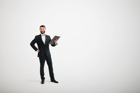 isolated man: full-length portrait of smiley businessman with open black folder over light grey background