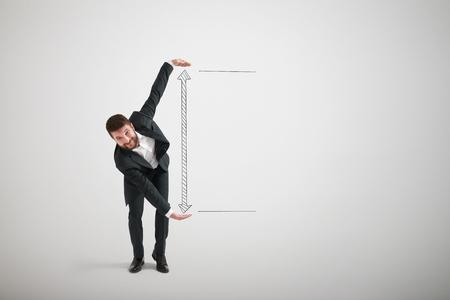 personas de pie: hombre de negocios sonriente mostrando gran flecha entre sus manos. copyspace vacío para el texto Foto de archivo