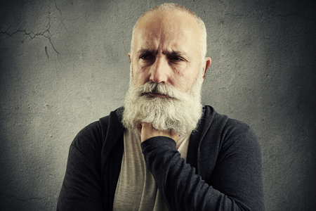 despondent: portrait of despondent senior man over grey backround Stock Photo