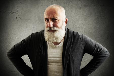 man with beard: trendy senior man looking at camera with interest over dark grey wall