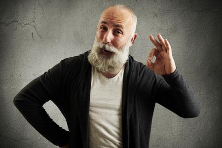 asombro: hombre mayor con barba muestra la muestra aceptable y mirando a la cámara sobre la pared gris Foto de archivo