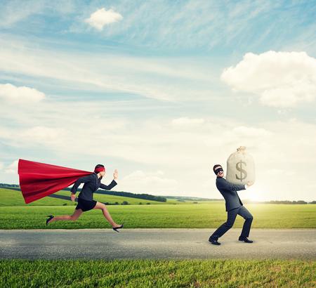 stole: ladrón contento robó la bolsa con el dinero y huir de superwoman en el camino al aire libre Foto de archivo