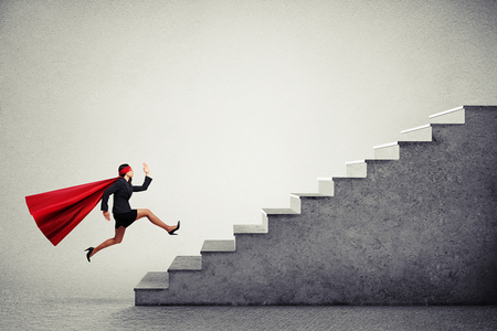 escalando: superwoman propósito en capa roja corriendo escaleras sobre fondo gris claro Foto de archivo