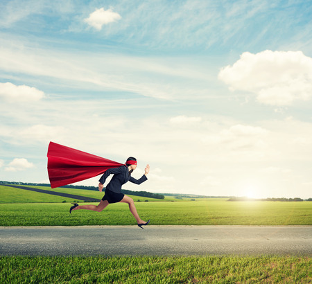 superwoman: concentrated superwoman in formal wear and red cloak with mask fast running on the road at outdoor Stock Photo