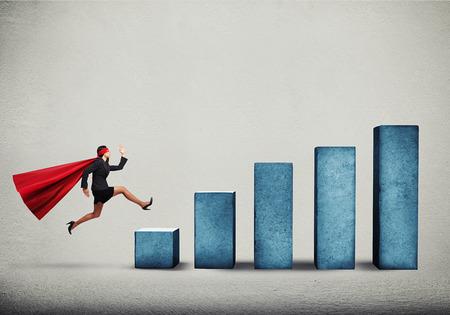 purposeful: purposeful businesswoman in superhero cloak running up on diagram over grey background