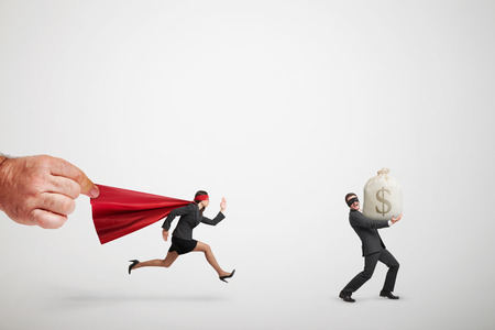 superwoman: big mans hand holding the red cloak of superwoman that chasing the thief with big bag of money over light grey background