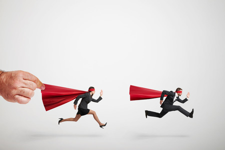 inhibit: two superheroes fast running but big mans hand holding red cloak of superwoman over light grey background Stock Photo