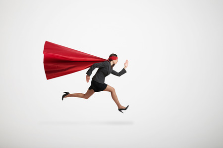 serious businesswoman wearing like superhero very fast running over light grey background Standard-Bild