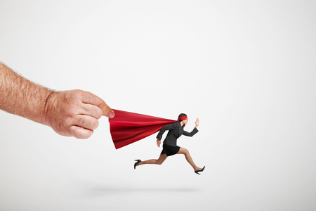 superwoman: big mans hand holding the red cloak of running superwoman over light grey background