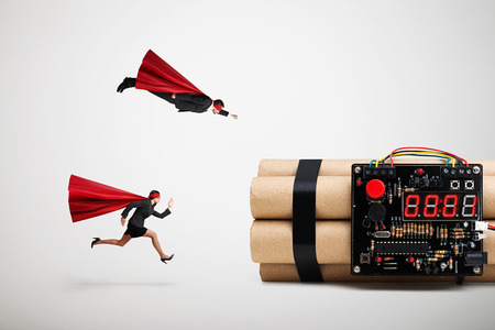 defuse: superman and superwoman hurry to defuse the bomb over light grey background Stock Photo