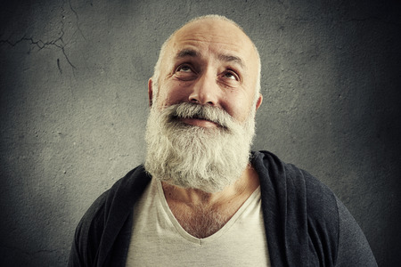 man looking: portrait of smiley bearded man looking up over dark background Stock Photo