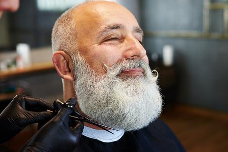 barber scissors: closeup portrait of bearded smiley man in barber shop. barber cutting beard with scissors