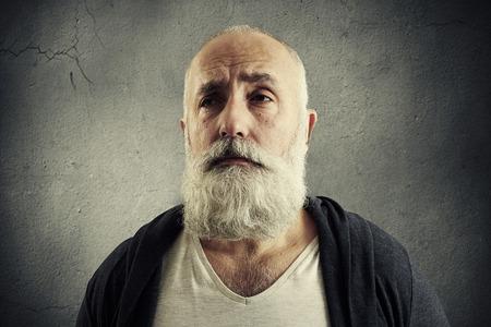 doleful: portrait of doleful senior man over dark wall Stock Photo