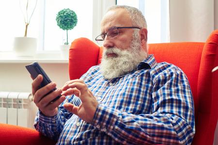 personas comunicandose: Hombre mayor serio con gafas sentado en la silla y utilizando su teléfono inteligente en el hogar Foto de archivo